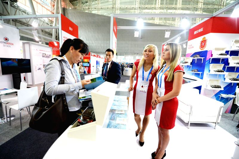 Russian exhibitors communicate with a Chinese dealer at the China-Russia Expo (CR Expo) in Harbin, capital of northeast China's Heilongjiang Province, June 30, 2014. .