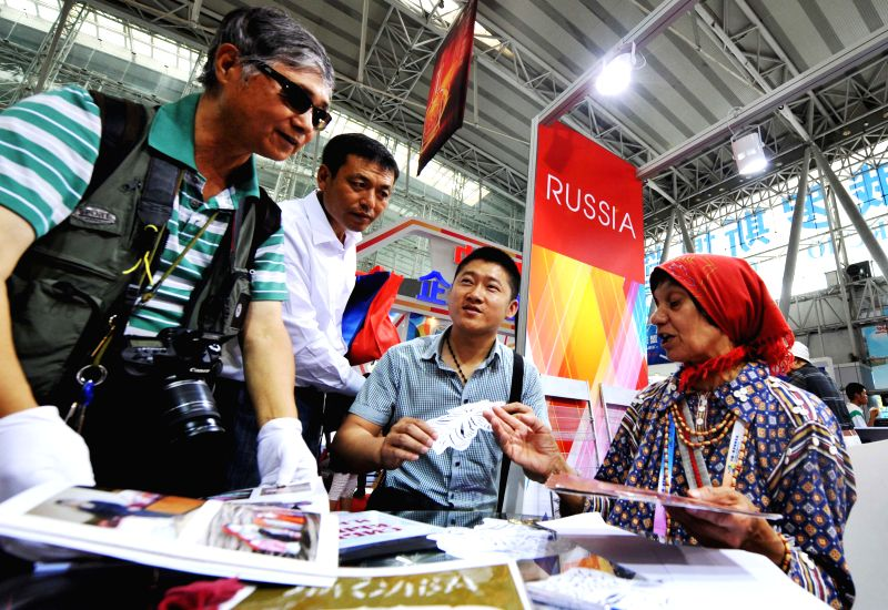 Visitors learn about paper-cut arts from a Russian folk artist at the China-Russia Expo (CR Expo) in Harbin, capital of northeast China's Heilongjiang Province, July .