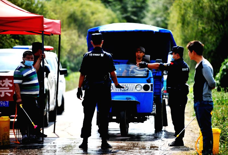 Local police inspect a tricycle at a checkpoint at Dongyue Village of Shuangcheng District of Harbin, capital of northeast China's Heilongjiang Province, Sept. 2, ...