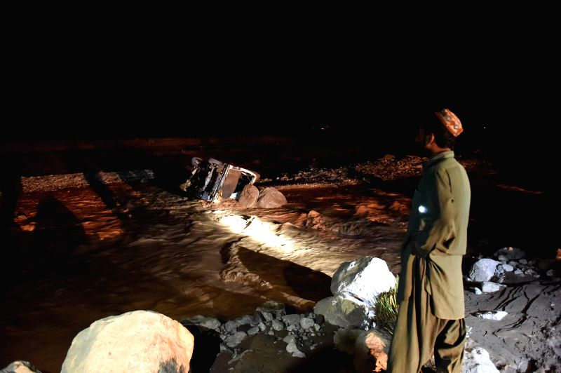 HARNAI, Aug. 7, 2016 - A local resident looks at a drowned vehicle in flood water in Harnai, southwest Pakistan, Aug. 7, 2016. At least 29 people were killed and scores others went missing as heavy ...