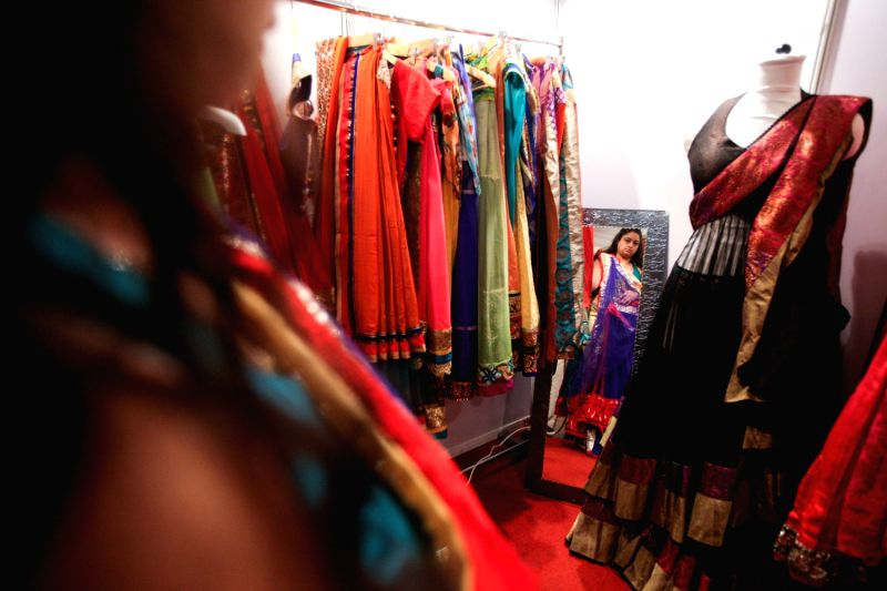 An exhibitor presents wedding costumes during the Big Fat Wedding exhibition in Gurgon of Haryana, India, Aug. 29, 2013. More than 30 exhibitors in India ...