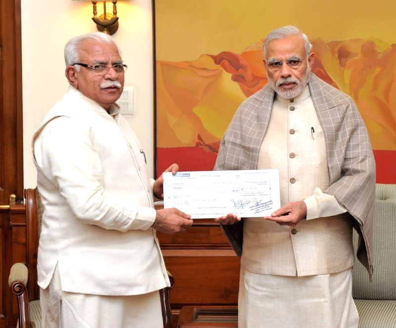 Haryana Chief Minister Manohar Lal Khattar presents a demand draft worth Rs. 5 crore to the Prime Minister Narendra Modi towards the Prime Minister's National Relief Fund (PMNRF), in New ... - Manohar Lal Khattar and Narendra Modi