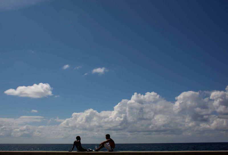 Cuban citizens rest at a pier, in Havana, capital of Cuba, on April 21, 2014.