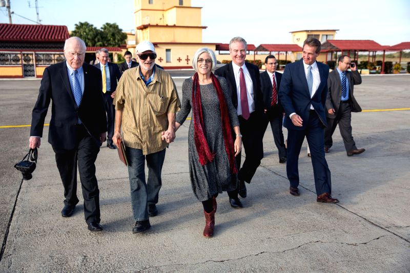 Photo provided by the White House shows U.S. contractor Alan Gross (2nd L Front) holding his wife's hand after being released in Havana, Cuba, on Dec. 17, 2014. ... - Alan Gross