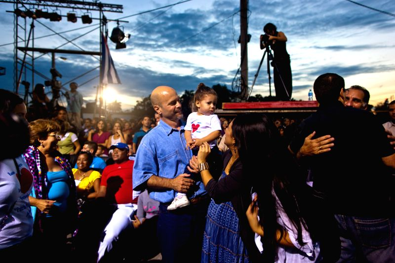 "Gerardo Hernandez(C), members of ""Cuban Five,"" holds a girl during a concert of Silvio Rodriguez in Havana, Cuba, Dec. 20, 2014. Cuban leader Raul Castro .."