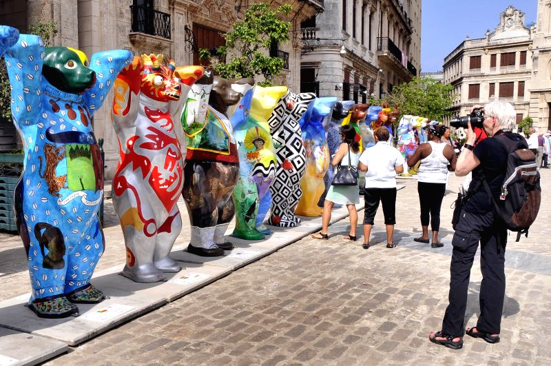"A visitor takes photos of the ""United Buddy Bears"" exhibition in Havana, Cuba, on Jan. 16, 2015. The exhibition aims to promote tolerance and understanding"