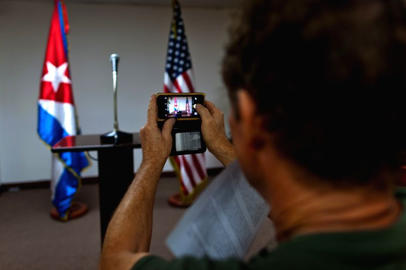 A journalist takes pictures of the national flags of Cuba (L) and the United States at the Convention Palace in Havana, Cuba, Jan. 22, 2015. Journalists from all ...