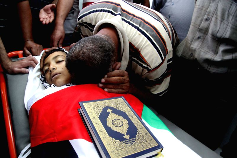 A relative of Palestinian boy Khalil Al-Anati, 10, mourns over his body at a hospital in the West Bank city of Hebron, on Aug. 10, 2014. Al-Anati was shot dead by ...