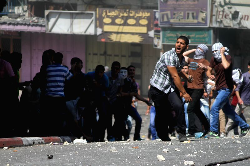 West Bank Palestinians hurl stones at Palestinian security officers who stop them from reaching an Israeli checkpoint during a rally in the West Bank city of Hebron .