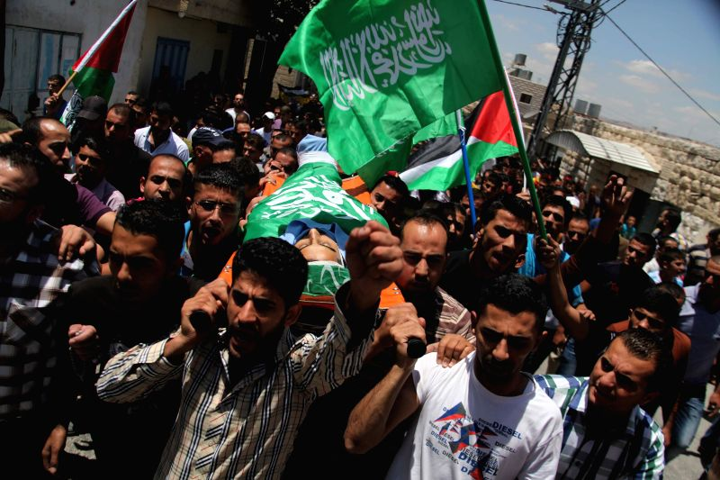 Palestinians  carry the body of Monir Badareen, 22, during his funeral in the West Bank city of Hebron, on July 14, 2014. The Palestinian young man was killed on ...