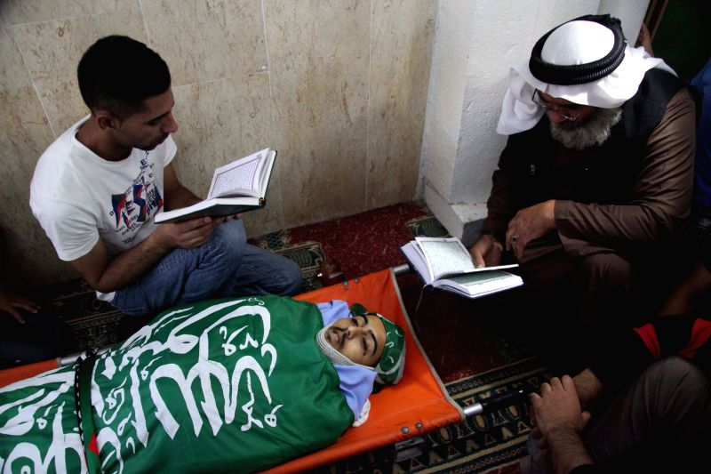 Palestinians read holy Quran over the body of Monir Badareen, 22, during his funeral in the West Bank city of Hebron, on July 14, 2014. The Palestinian young man was