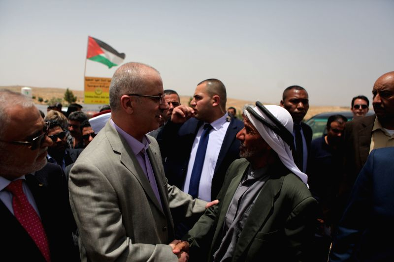 Palestinian Prime Minister Rami Hamdallah (2nd L) is greeted by residents as he arrives for a visit in the southern West Bank village of Sosia, which Israel intends ... - Rami Hamdallah