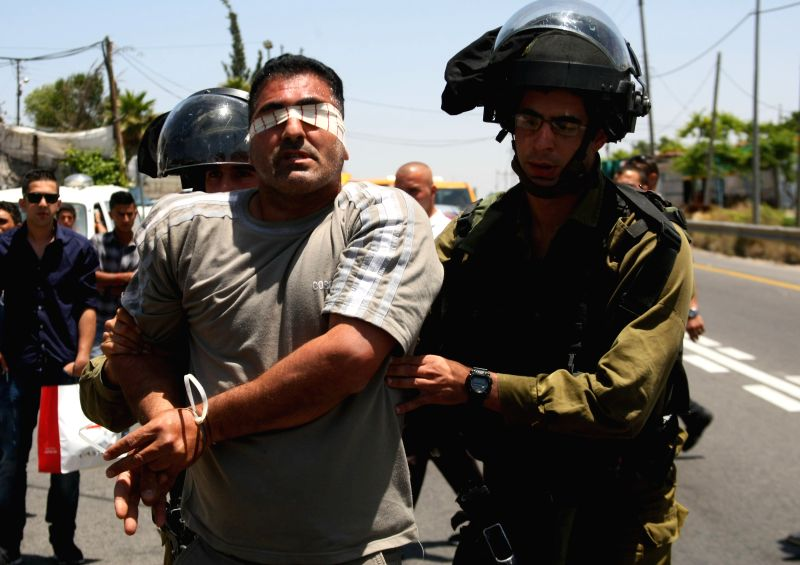 Israeli security forces arrest a Palestinian near a main street between Hebron and Jerusalem, during a protest marking the 66th anniversary of Nakba in the West Bank ..