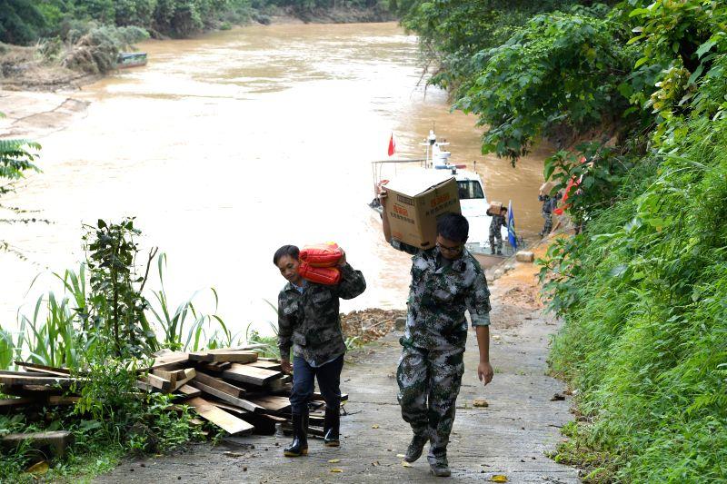 HECHI, July 17, 2019 (Xinhua) -- Photo taken on July 16, 2019 shows rescuers carrying disaster relief materials off boat in Aidong Township of Donglan County in Hechi, south China's Guangxi Zhuang Autonomous Region. (Xinhua/Zhou Hua/IANS)