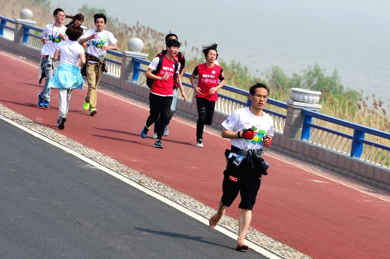 People take part in a spring walking convention in Hefei, capital of east China's Anhui Province, April 11, 2015. A spring walking convention was held in Hefei on ...