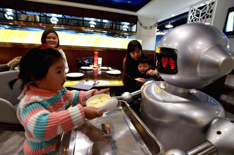 A robot waiter serves a dish to a girl at a restaurant in Hefei, capital of east China's Anhui Province, Jan. 20, 2015. The restaurant is staffed with robot waiters ..