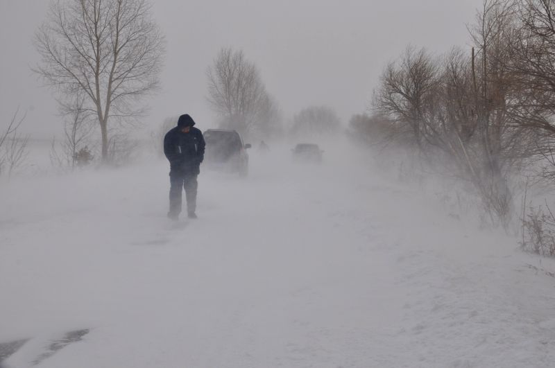 A man walks in snow in Heihe, northeast China's Heilongjiang Province, Dec. 1, 2014.  A strong cold front will sweep central and east China, bringing sharp temperature drops on Monday and ...