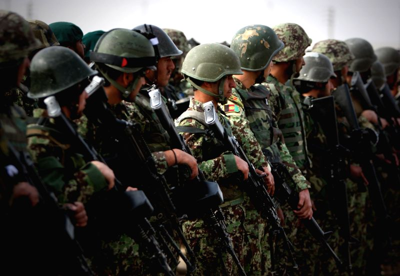 Afghan army soldiers stand guard during a ceremony marking the end of security transition from NATO-led troops to Afghan army in Gereshk district in the southern ...