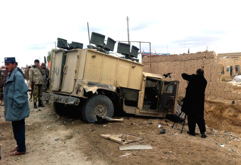 Afghan policemen gather around a destroyed police vehicle following a suicide car bombing in Helmand province in southern Afghanistan, Jan. 22, 2015. Three persons .