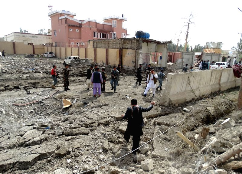 Afghan policemen inspect the site of suicide car bombing in Helmand province, southern Afghanistan, March 18, 2015. Seven civilians were killed and 46 others ...