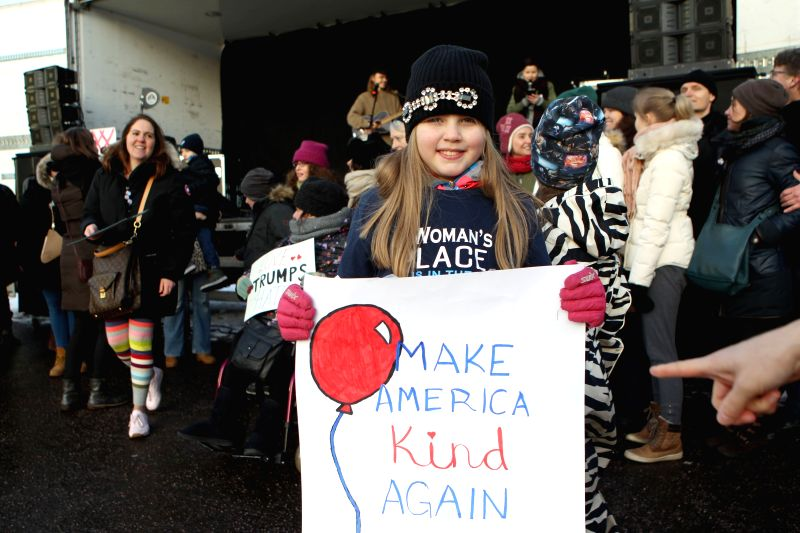 """HELSINKI, Jan. 21, 2017 - A protester holds a placard reading """"make America kind again"""" in Helsinki, Finland on Jan. 21, 2017. Some 500 people gathered in central Helsinki to call for ..."""