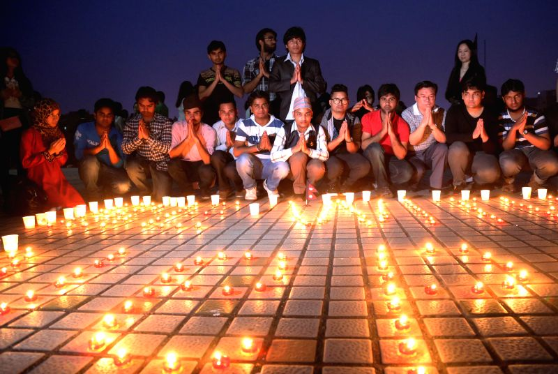 Students light candles and pray for people trapped in Nepal earthquake at the University of South China in Hengyang City, central China's Hunan Province, April ...