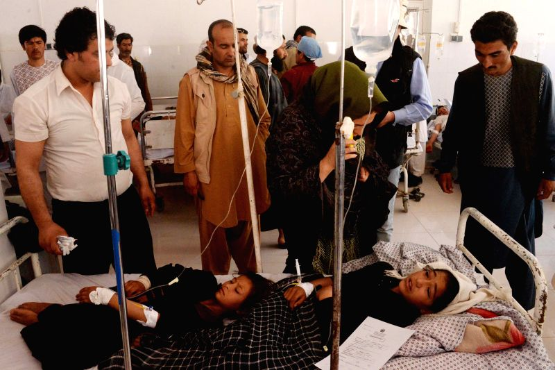 Afghan school students receive first aid after inhaling some mysterious poisonous gas at their school in Herat province, Afghanistan, April 11, 2015. Around 100 ...