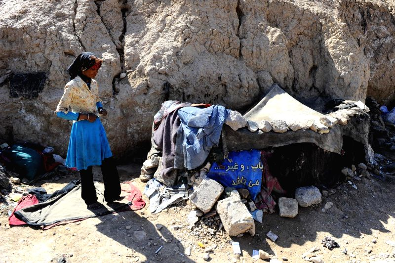 An Afghan drug addicted woman walks at a slum area in Herat province, western of Afghanistan, April 26, 2014.