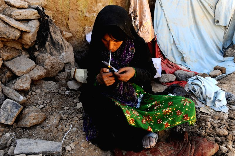 An Afghan drug addicted woman smokes heroin at a slum area in Herat province, western of Afghanistan, April 26, 2014.