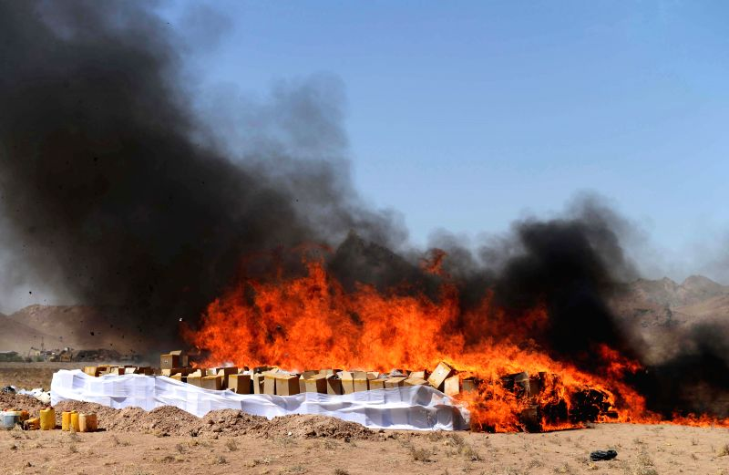 Smoke rises from burning drugs in Herat province, western Afghanistan, on Aug. 31, 2014. The government of Afghanistan destroys 21 tons of narcotics in Herat province