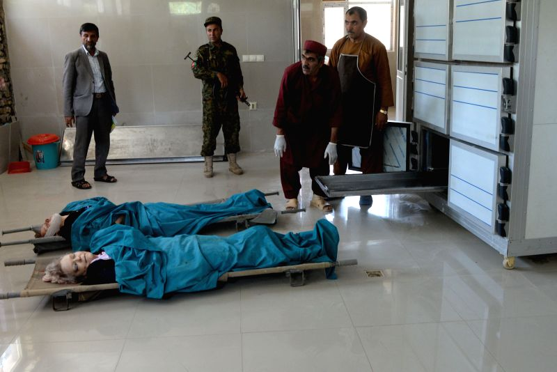 Dead bodies of two foreigners are seen at a hospital in Herat province in western Afghanistan on July 24, 2014. Two foreign aid workers were shot dead in a drive-by ..