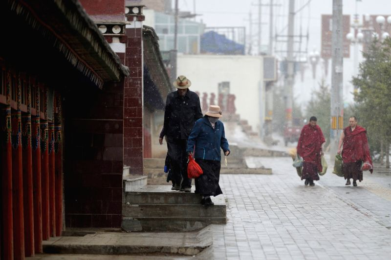 Citizens brave snow as they walk on a street in Hezuo City of Gannan Tibet Autonomous Prefecture, northwest China's Gansu Province, May 9, 2014. A cold front brought ...