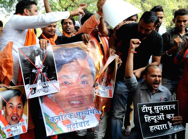 Hindu Sena activists burn posters of Karnataka Chief Minister Siddaramaiah during a demonstration against birth anniversary celebrations of Tipu Sultan; in New Delhi, on Nov 13, 2015. - Siddaramaiah