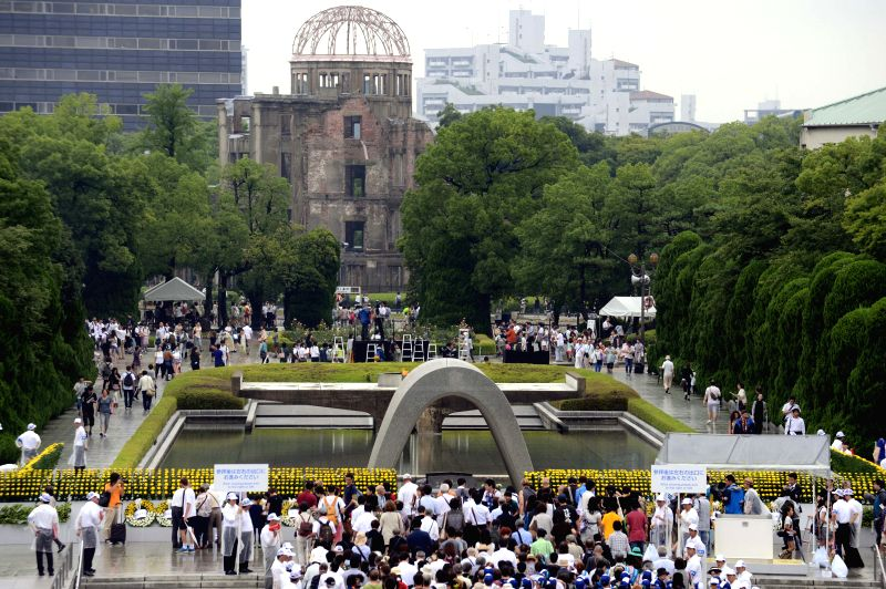 People gather in front of the Atomic Bomb Dome (background) at the Peace Memorial Park to pray for the victims of the 1945 atomic bombing in Hiroshima on August .