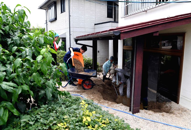 HIROSHIMA, July 11, 2018 - People clear a swamped house in Kure, Hiroshima, southwestern Japan, July 11, 2018. The death toll in the wake of torrential rains battering western Japan and causing ...