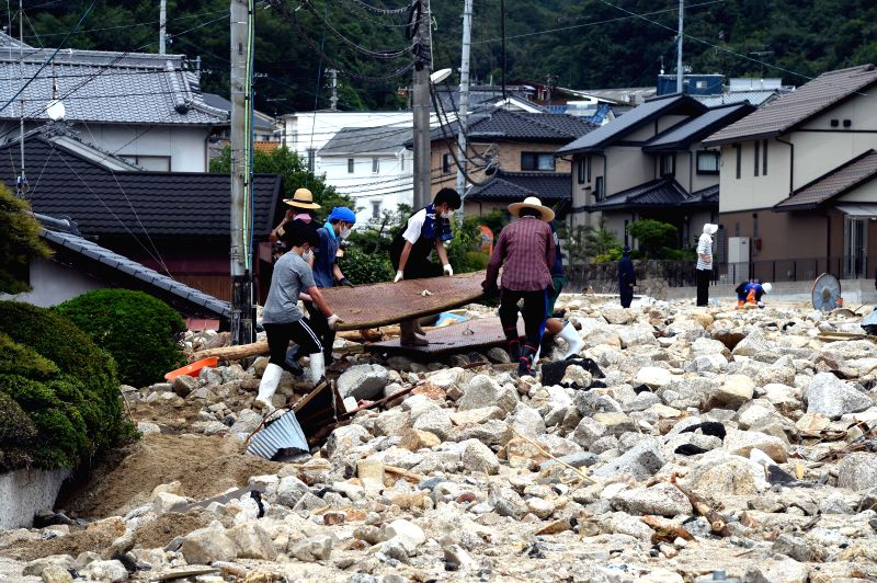 HIROSHIMA, July 11, 2018 - People clear submerged houses in Kure, Hiroshima, southwestern Japan, July 11, 2018. The death toll in the wake of torrential rains battering western Japan and causing ...
