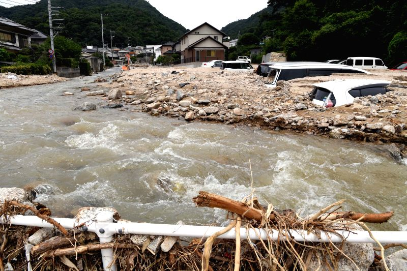 HIROSHIMA, July 11, 2018 - Photo taken on July 11, 2018, shows floodwater flowing by a village in Kure, Hiroshima, southwestern Japan. The death toll in the wake of torrential rains battering western ...