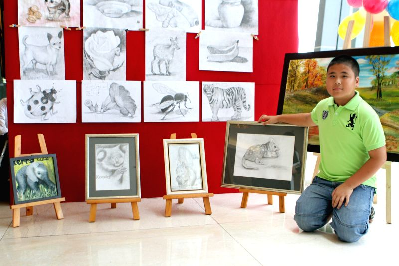 Ho Chi Minh city: A young painter poses for photos with his painting during a charity art exhibition in Ho Chi Minh city, Vietnam, Nov. 22, 2014. The exhibition held here on Saturday shows excellent .