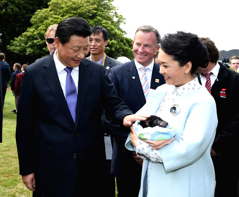 Hobart (Australia): Chinese President Xi Jinping and his wife Peng Liyuan pet a Tasmanian devil after planting a tree with students of a primary school in Tasmania state, Australia, Nov. 18, 2014.  ..