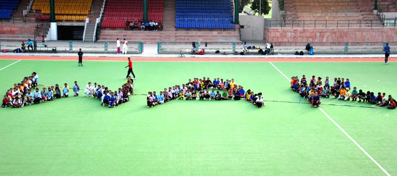 Hockey players sit in a 'WAR' formation with their hockey sticks striking the word to condemn recent militant attacks in Iraq, in Amritsar on June 20, 2014.