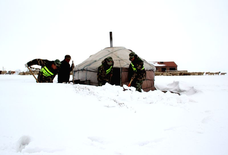 Police officers help a herdsman clear snow around his yurt on a grassland in East Ujimqin Banner, north China's Inner Mogolia Autonomous Region, May 4, 2014. Some ...