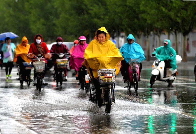People ride bicycle in rain in Hohhot, capital of north China's Inner Mongolia Autonomous Region, May 9, 2014. A rainfall hit Hohhot on Thursday night and Friday.  ...