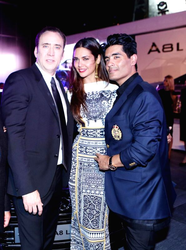 Hollywood actor Nicholas Cage, Esha Gupta and Manish Malhotra during the launch of Audi A8L in Dubai. - Nicholas Cage and Manish Malhotra