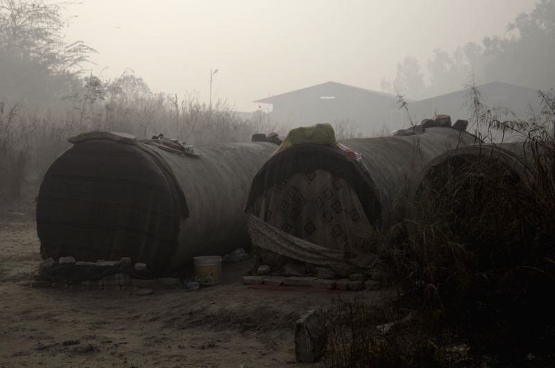 """Homeless turn water-pipes into their """"homes"""" near a night shelter in New Delhi, on Dec 7, 2015."""
