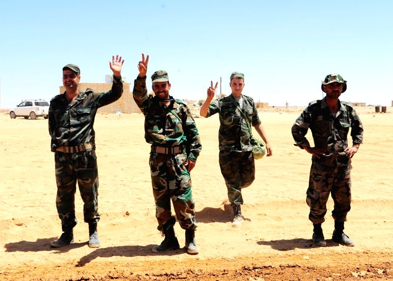 HOMS, June 13, 2017 - Syrian soldiers gesture in the Syrian desert at the countryside of the central Homs province near the Syrian-Iraqi borders, on June 12, 2017. The Syrian army recently announced ...