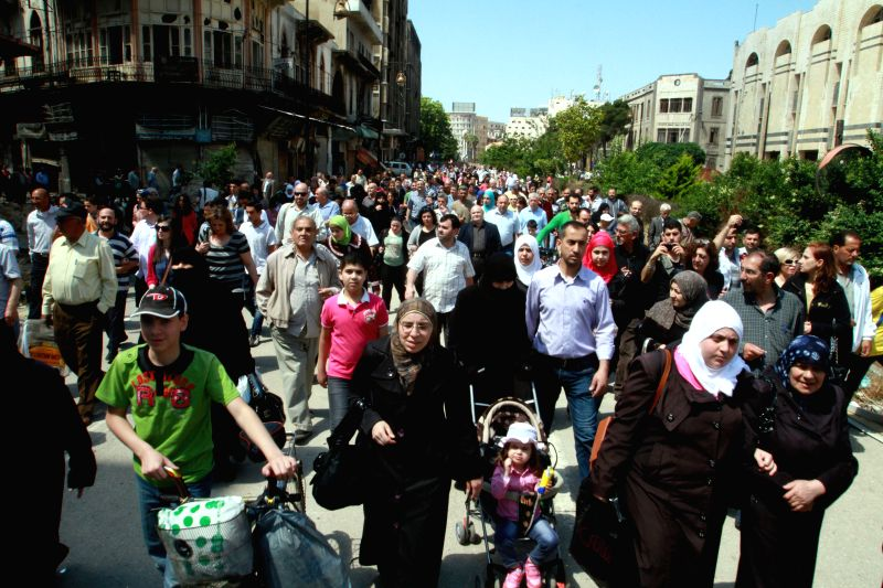 Residents carry their belongings in al-Hamidieh neighborhood in the old city of Homs, Syria, on Saturday, May 10, 2014. The Governor of Syria's central province of Homs