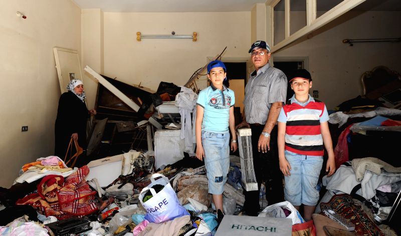 A family collect belongings after returning home in the old city of Homs, Syria, May 15, 2014. The war-torn old city of Homs are left empty of arms and armed rebels but