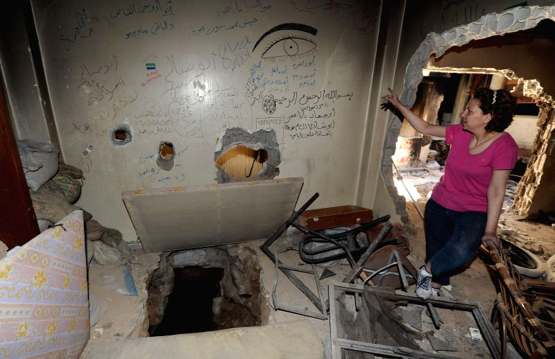 A woman looks at a tunnel dug by rebels at her home in the old city of Homs, Syria, May 15, 2014. The war-torn old city of Homs are left empty of arms and armed rebels .
