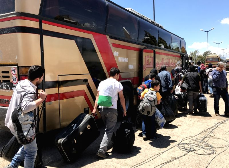 HOMS, May 21, 2017 - Rebels's families and civilians walk to embark on a bus transporting them from the al-Waer neighborhood in the central city of Homs toward rebel-held areas in northern Syria on ...