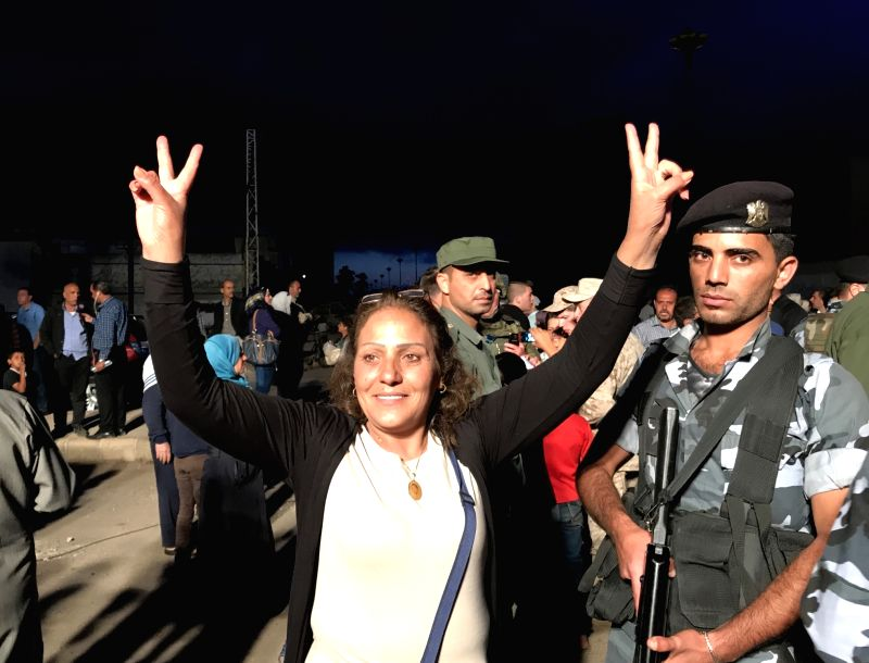 HOMS (SYRIA), May 21, 2017 A Syrian woman flashes the victory sign in the al-Waer neighborhood in Homs city, Syria, on May 21, 2017. The last batch of rebels evacuated their last ...